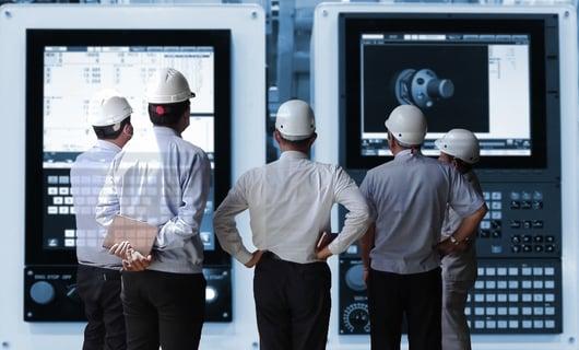 shutterstock_5 hardhat factory men looking at large displays